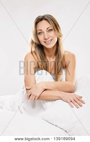 Nice pretty girl smiling in bed in the morning on white background