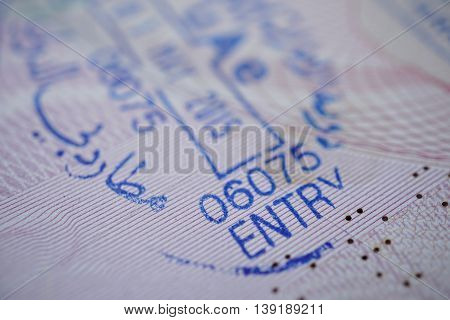 Passport stamp with a caption Entry in blue ink as a part of Visa page