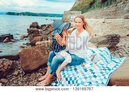 happy mother and daughter spending time together on the beach on summer vacation. Happy family traveling cozy mood.
