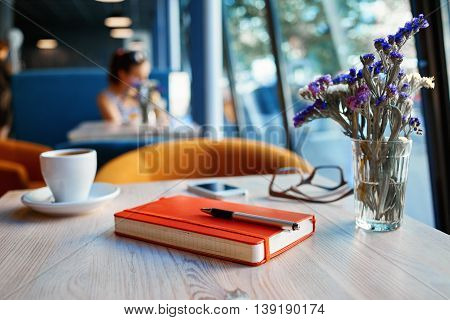 free table with cup, notebook and eyeglasses at a table made of wood . in the background a bright window with bright daylight. business or education concept