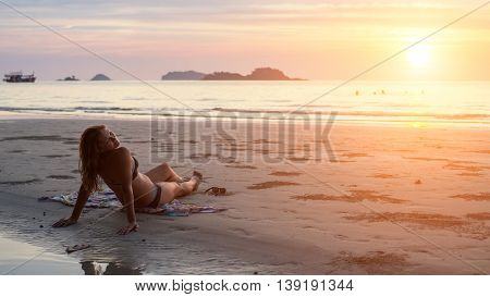 Young woman lying on the beach in the setting sun.