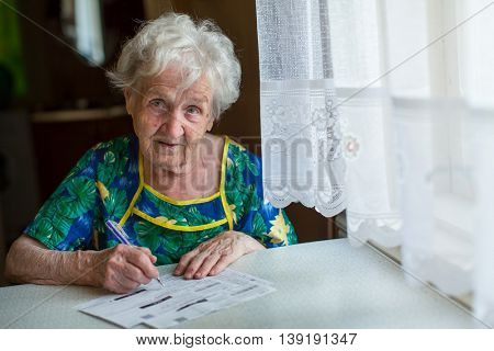 Retired woman fills out utility bills sitting at home behind a table.