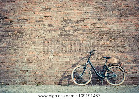 Black retro vintage bicycle with old brick wall and copy space. Retro bicycle with basket in front of the old brick wall. Old photo effect applied. Toned.