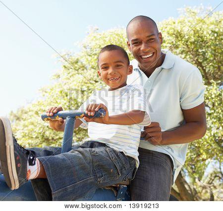 Vater und Sohn auf Wippe im Park Reiten