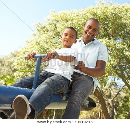 Father and Son Riding On SeeSaw In Park