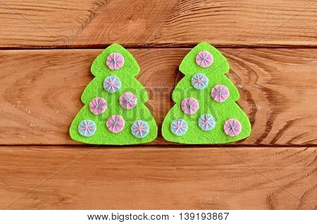 Green felt tree with pink and blue balls on a wooden background. Christmas tree felt sew. Scrapbook embellishment. Home crafts tutorial. Sewing lesson. Step. Top view. Closeup