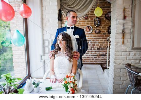 Wedding Couple Sitting At A Table In A Cafe