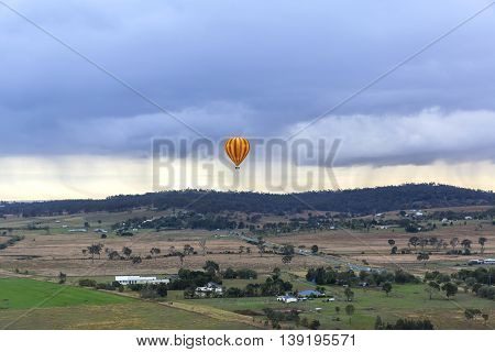 Red and Yellow striped hot air balloon in the air floating across farm land on a cloudy day