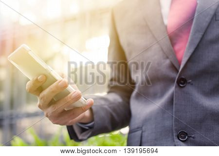 Business man using a cellphone (focus on cellphone)