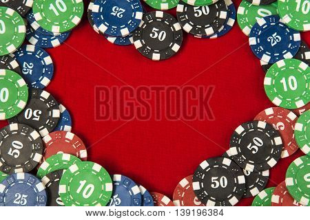 Gambling chips frame around the red card table background in the shape of a heart