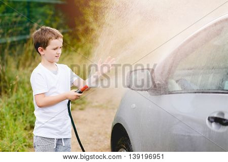 Little Boy Washing Silver Car In The Garden