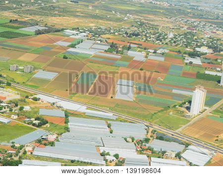 Aerial view from airplane on ground with fields, forest and sea