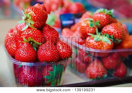 Fresh strawberry at market in plastic boxes, local food healthy background in vintage hipster style
