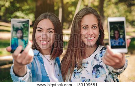 Portrait of two women taking selfie photos with their smartphones over a forest background
