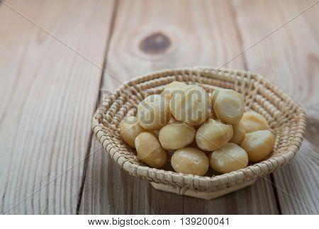 Macadamia in basket weave on wooden floor.Focus on macadamia.