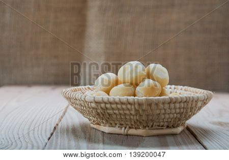 Macadamia in basket weave on wooden floor with sackcloth background.Focus on macadamia.