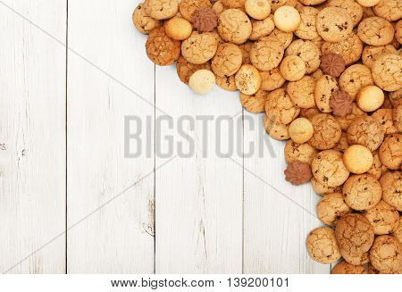 Cookies and sweet biscuits at white wood, background with copy space. Oatmeal and chocolate drops cookies border, dessert for tea.