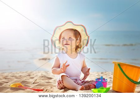 one year old girl shouting at the sea with bucket