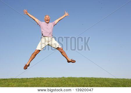 Senior hombre que salta en el aire