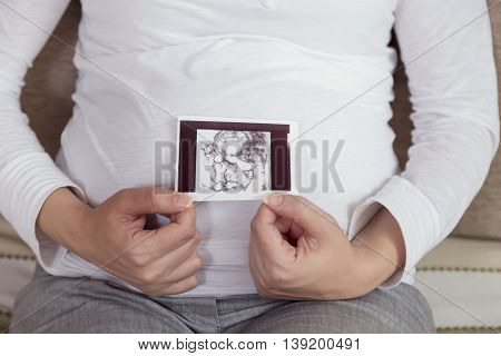 Pregnant woman sitting on a couch in a living room of an apartment holding and looking at an ultrasound photo of her baby