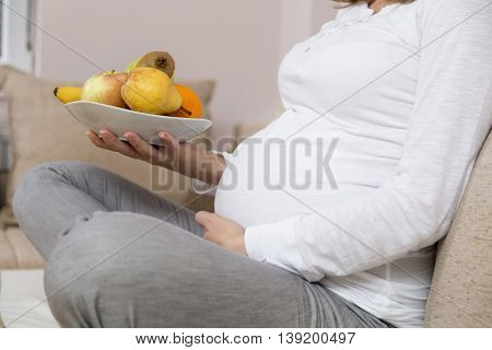 Close up of a pregnant woman's belly while she is sitting on a couch in a living room and holding a bowl of fruit