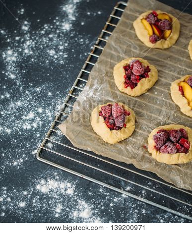 Delicious ready for baking mini tarts with fresh berries and fruits on food lattice