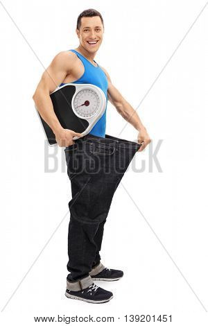Full length portrait of a handsome guy in an oversized pair of jeans holding a weight scale isolated on white background