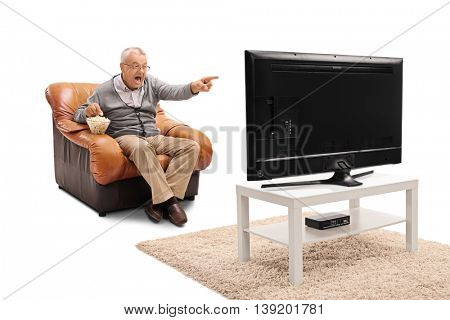 Happy mature man eating popcorn seated on an armchair and watching TV isolated on white background