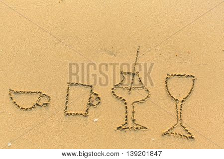 Glasses and crockery are drawn in the beach sand.