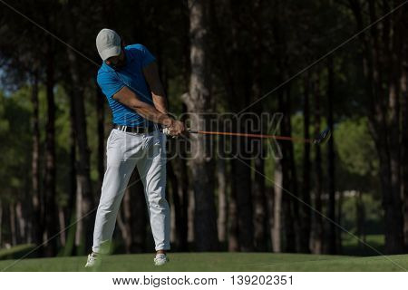golf player hitting shot with club on course at beautiful morning