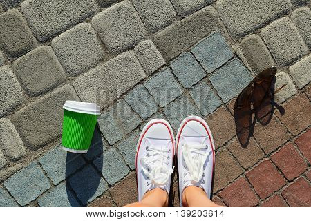 White Gumshoes, Disposable Cup And Sunglasses On The Background Pavement