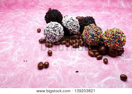 Chocolate ball/candies collection with colorful sprinkles, jimmies for cake decoration or ice cream topping,with background of pink mulberry paper.