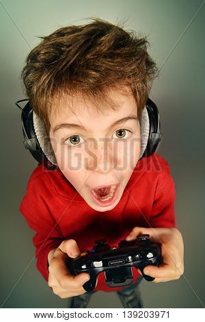 Funny boy gamer with a controller and headphones. Studio shot.