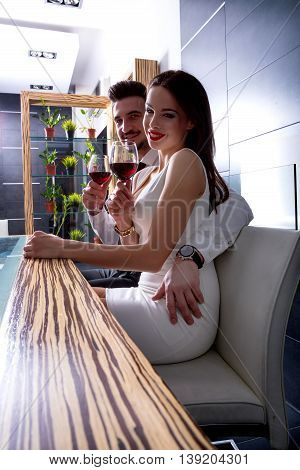 A romantic couple with a glass of wine in the dining room.