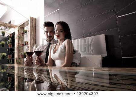 A romantic couple with a glass of wine in the dining room
