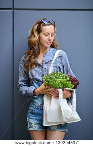 Young Stylish Woman Is Holding In Their Hands A Linen Bag With Lettuce Salad