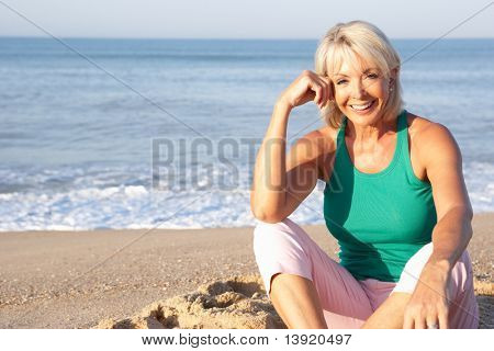 Senior woman sitting on beach relaxing