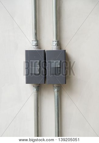 Close up of modern light switch on concrete wall.