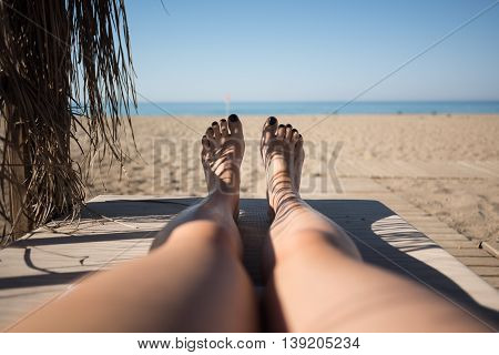Female feet on lounge first person view from bungalow on the sea with sand beach