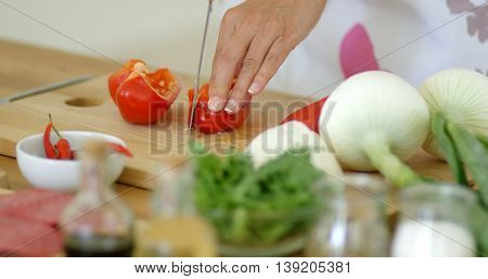 Housewife chopping a fresh red bell pepper
