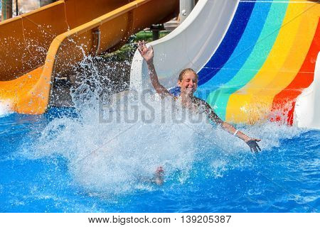 Happy kid on water slide at water park hands up. There are some water slides with flowing splash water in aqua park. Summer water park holiday. Outdoor.