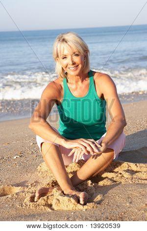 Senior woman sitting on beach relaxing