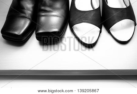 Close up of woman leather shoe and man leather shoe on wooden floor. Black and white tone.