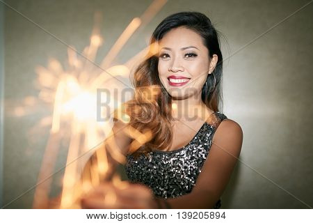 Happy Asian party girl holding bengal light