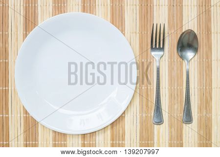 Closeup white ceramic dish with stainless fork and spoon on wood mat textured background on dining table in top view
