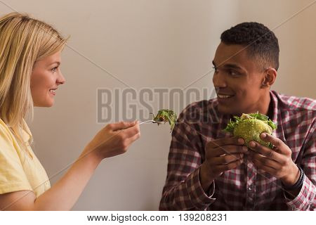 Happy couple spending free time in vegan restaurant or cafe. Lady feeding her boy-friend with vegan salad. Vegan concept.