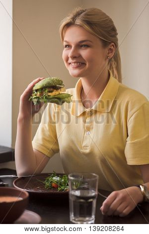 Closeup of lady holding vegan burger in hands while sitting in vegan restaurant or cafe. Hunger, healthy, meal concepts.