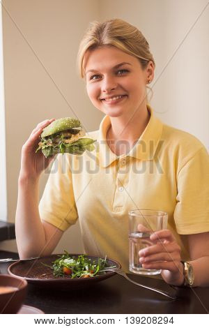 Hunger, healthy, meal concepts. Closeup of lady holding vegan burger in hands while sitting in vegan restaurant or cafe.
