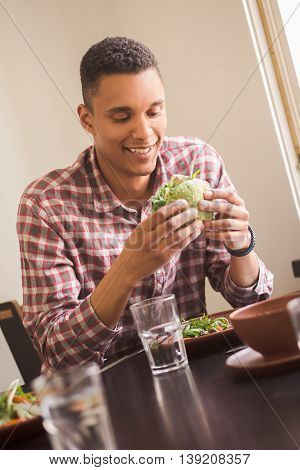 Picture of smiling man sitting at table in vegan restaurant or cafe. Happy man looking at his vegan burger. Healthy and delicious food concepts.