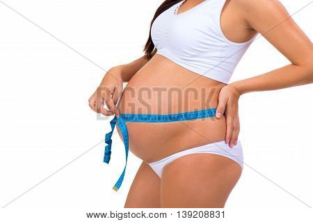 Pregnancy. Close-up of pregnant belly. Measuring volume of tummy measuring tape